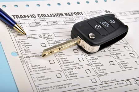 car key and pen on a traffic collision report Stock Photo