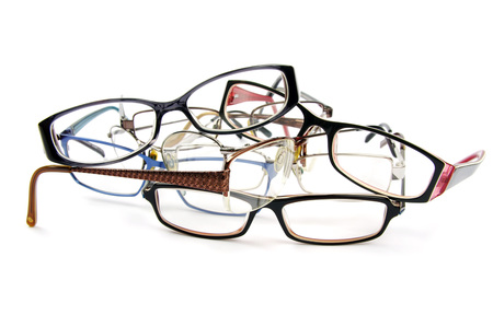 reading glasses in a pile on a white background