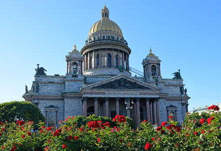 leningradskaya: St. Isaacs Cathedral on a background of red roses on the square bright Sunny day under blue sky
