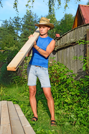 A young man with the pine Board on his shoulder about piles of boards on the plot in the summer on a Sunny day