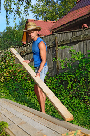 grass plot: Young athletic man in balomenou hat puts a pine Board on the stack in the village