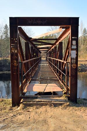 pedestrian bridges: Metal pedestrian bridge across the river Oredezh in the village of Vyritsa Stock Photo