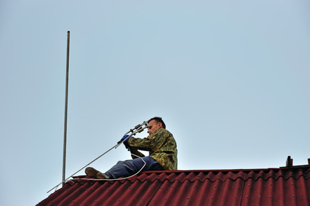 mounts: A worker mounts a individual UHF television antenna on the roof of the country house