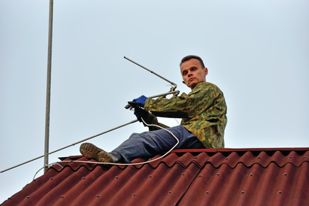 A worker mounts a individual UHF television antenna on the roof of the country house