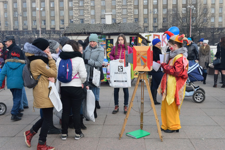 buffoon: ST.PETERSBURG, RUSSIA - MARCH 13, 2016: Children and adolescents next to the actress is a buffoon and a fake vintage camera on the holiday of Maslenitsa at Moscow square
