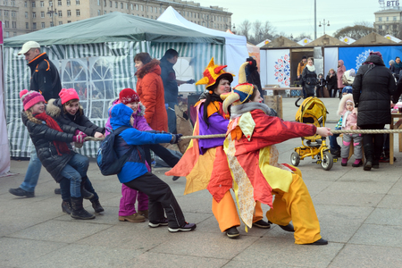 maslenitsa: ST.PETERSBURG, RUSSIA - MARCH 13, 2016: Children with the actress-comedian pull the rope on the holiday of Maslenitsa at Moscow square Editorial