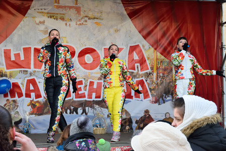 spectators: ST.PETERSBURG, RUSSIA - MARCH 13, 2016: The spectators in the performance of vocal female trio in multi-colored jumpsuits on the street on the holiday of Maslenitsa at Moscow square Editorial