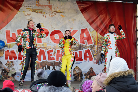maslenitsa: ST.PETERSBURG, RUSSIA - MARCH 13, 2016: The spectators in the performance of vocal female trio in multi-colored jumpsuits on the street on the holiday of Maslenitsa at Moscow square Editorial