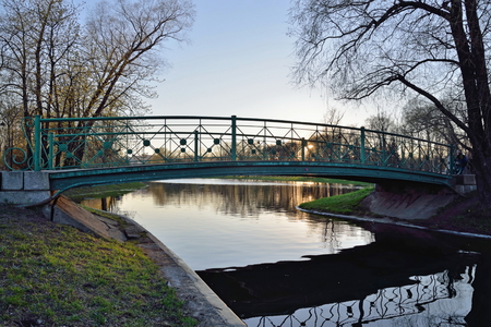 pedestrian bridges: Bridge over a pond at sunset in the city Park of the Victory in Saint-Petersburg Stock Photo