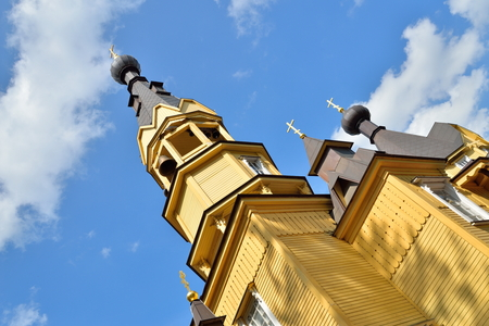 The bell tower of the Church of the Holy apostles Peter and Paul in the village of Vyritsa in the Leningrad region on the background of blue sky .
