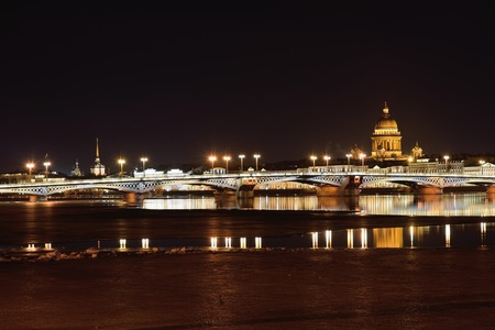 View of the Annunciation bridge, the English embankment of the river Neva, St. Isaacs Cathedral from Vasilyevsky island at night in the spring in St. Petersburg