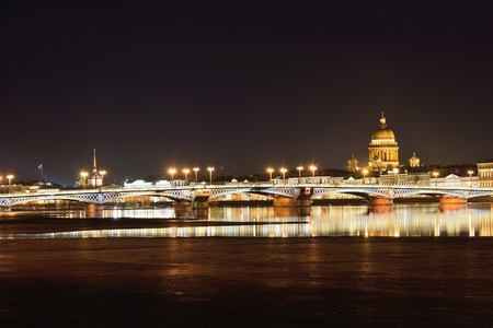 View of the Annunciation bridge, the English embankment, St. Isaacs Cathedral from Vasilyevsky island at night in the spring in St. Petersburg