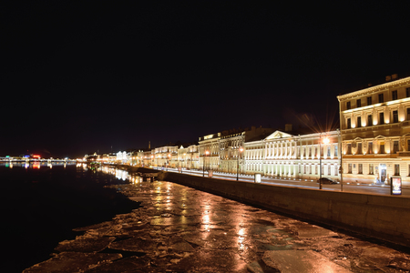 floating bridge: Night view on English embankment and Neva river with floating ice floes with Blagoveshchensky bridge in St. Petersburg Stock Photo