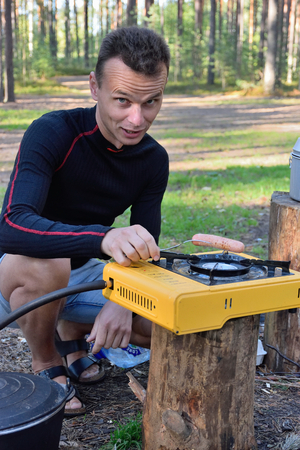 leningradskaya: A tourist in the woods roasts a sausage on gas from the portable gas stove in the woods