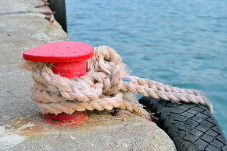 bollard: Red stand on the pier with a rope and tyre. Crimea. Stock Photo