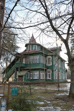 Green wooden two-storey house with a turret on the territory of the kindergarten in the village of Vyritsa of the Leningrad region Stock Photo
