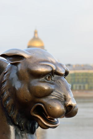 Gryphon on a background of St. Isaacs Cathedral and Neva river in St. Petersburg