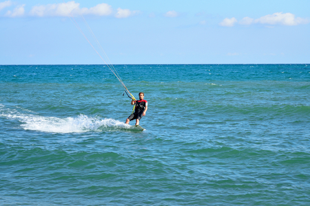 KARADAG, CRIMEA ON 17 SEPTEMBER 2016: A man in a wetsuit floating on the Board while holding the kite. Crimea Stock Photo
