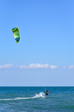 KARADAG, CRIMEA ON 17 SEPTEMBER 2016: A man in a wetsuit floating on a Board with a kite. Crimea