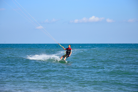 A man in a wetsuit floating on the Board while holding the kite. Crimea Stock Photo