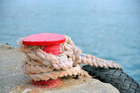 Red stand on the pier with a rope and tyre. Crimea. Stock Photo