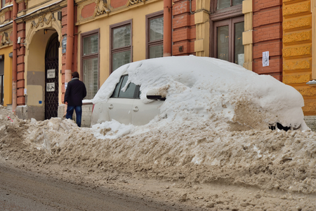 mud and snow: SAINT-PETERSBURG, RUSSIA - NOVEMBER 15, 2016: Car covered with snow on the embankment of the river Moika