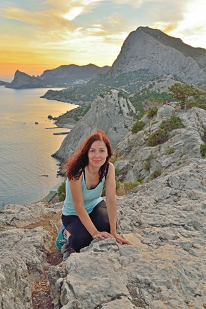sudak: The girl sits on a high hill by the sea at sunset. Sudak. Crimea