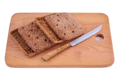 morsel: Rye morsel of bread on a wooden Board with a knife.