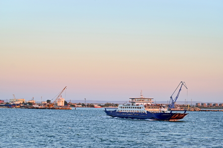 kavkaz: ANAPA, RUSSIA - 2016 12 SEPTEMBER: View of the pier of port of Kavkaz and floating ferry at sunset. Russia