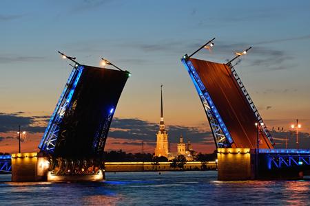 La fortaleza de Pedro y Pablo en el objetivo separó el puente de Palacio en el río Neva en San Petersburgo durante las noches blancas contra la puesta de sol roja. El agua reflejaba las luces de la calle y las luces del puente. Foto de archivo