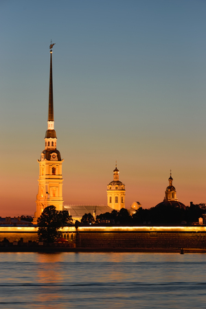 Peter and Paul fortress with the Palace promenade at sunset on a background of pure pink sky with reflection in the water of the Neva river during the white nights in St. Petersburg closeup.