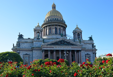 St. Isaacs Cathedral on a background of red roses on the square bright Sunny day under blue sky.