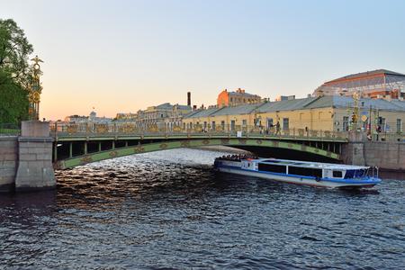 Pleasure boat sails under Panteleymonovsky bridge across the Fontanka  in Saint-Petersburg Фото со стока