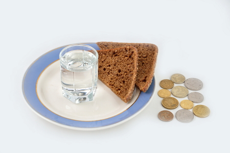trifle: A shot of vodka and rye bread on the background of coins.