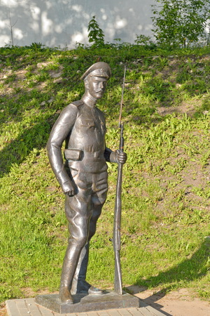 A statue of a soldier with a rifle on the embankment of the river great