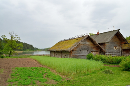 The garden and the old Russian log hut in Pushkin Mikhailovskoe summer cloudy day