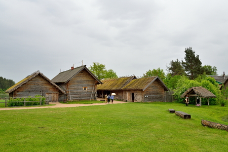 Tourists visiting the old log house in the Pushkin Mikhailovskoe summer cloudy day Stock Photo