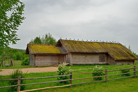 Old wooden log barn in the Museum of Pushkin Mikhailovskoe village summer cloudy day Banque d'images