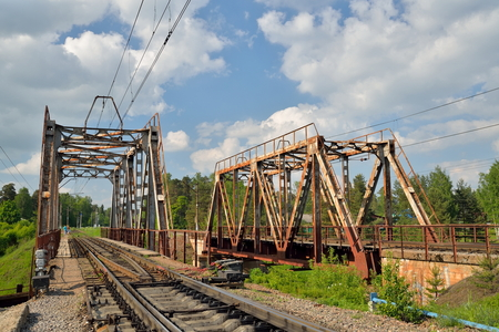 Railway bridge across the river and the rails with the arrow in Vyritsa in the summer Stock Photo