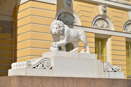 Stone lion with a ball at the main entrance to the Russian Museum in the summer