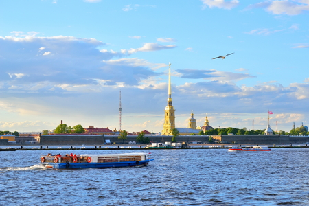 Tourist boats on the Neva river on the background of the fortress summer evening in Saint-Petersburg.