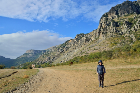 The boy is on a mountain road in the valley of ghosts in the vicinity of Alushta. Crimea