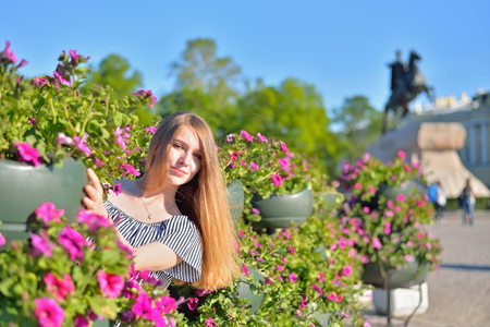 A young girl at the flower beds on the background of the monument bronze Horseman in Saint-Petersburg.