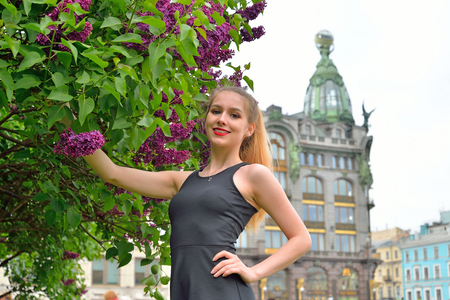 Beautiful girl smiling Bush of purple lilacs in the background of the book - singer in Saint-Petersburg