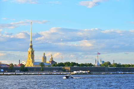 The speedboat floats on the Neva river on the background of the Peter and Paul fortress in summer in Saint-Petersburg.