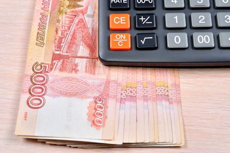 Russische bankbiljetten vijfduizend roebels en de rekenmachine liggen op tafel. Bedrijfsstilleven