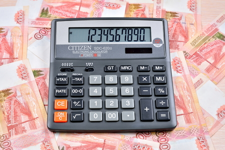 Black calculator lies on the Russian banknotes five thousand rubles. Business still life Imagens