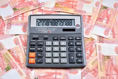 Zwarte rekenmachine staat op de Russische bankbiljetten vijfduizend roebel. Bedrijfsstilleven