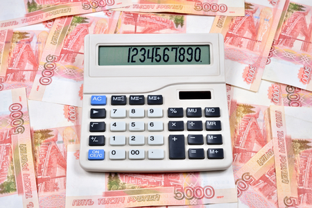White calculator is on the Russian banknotes five thousand rubles. Business still life Imagens