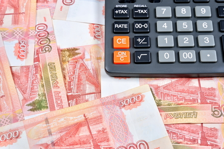 Gray calculator is on the Russian banknotes five thousand rubles. Business still life